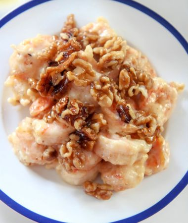 honey walnut shrimp on a white and blue plate up close.