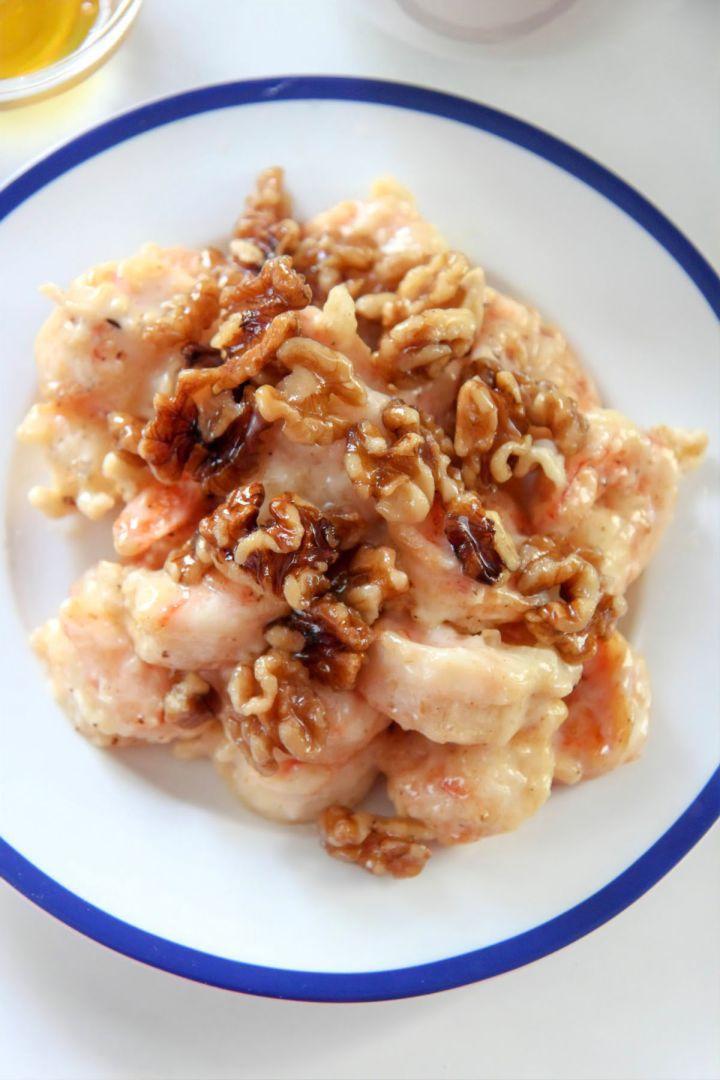 honey walnut shrimp on a white and blue plate up close.