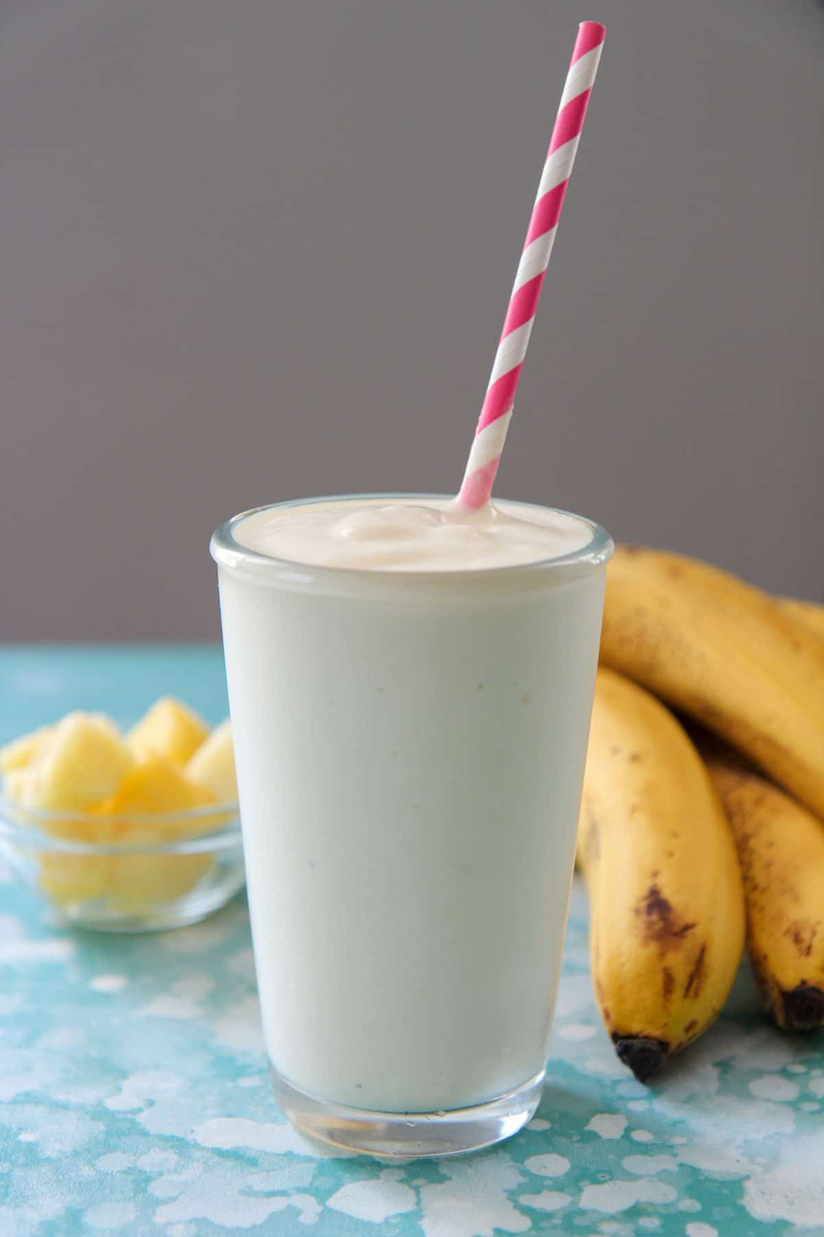 pineapple smoothie in a tall glass with a pink and white straw and bananas and pineapples in the background.