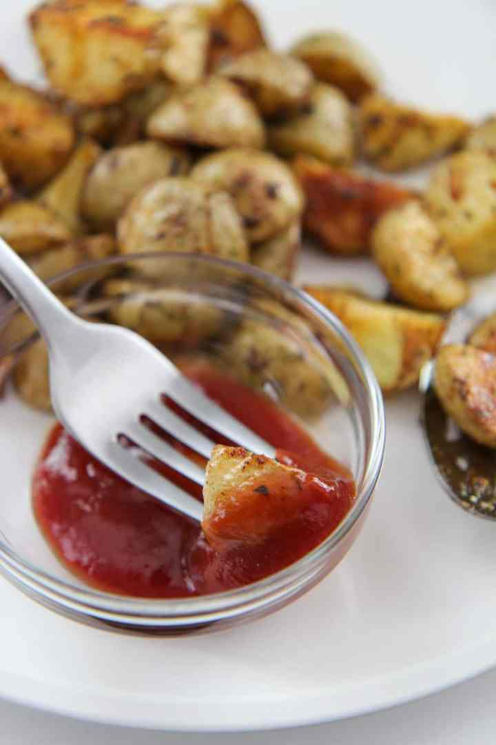 potato dipped in ketchup using a fork