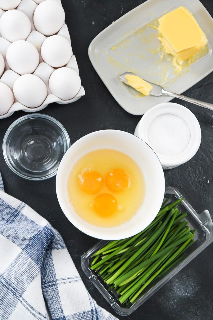 eggs in a bowl, chives, salt, water, and a blue and white cloth