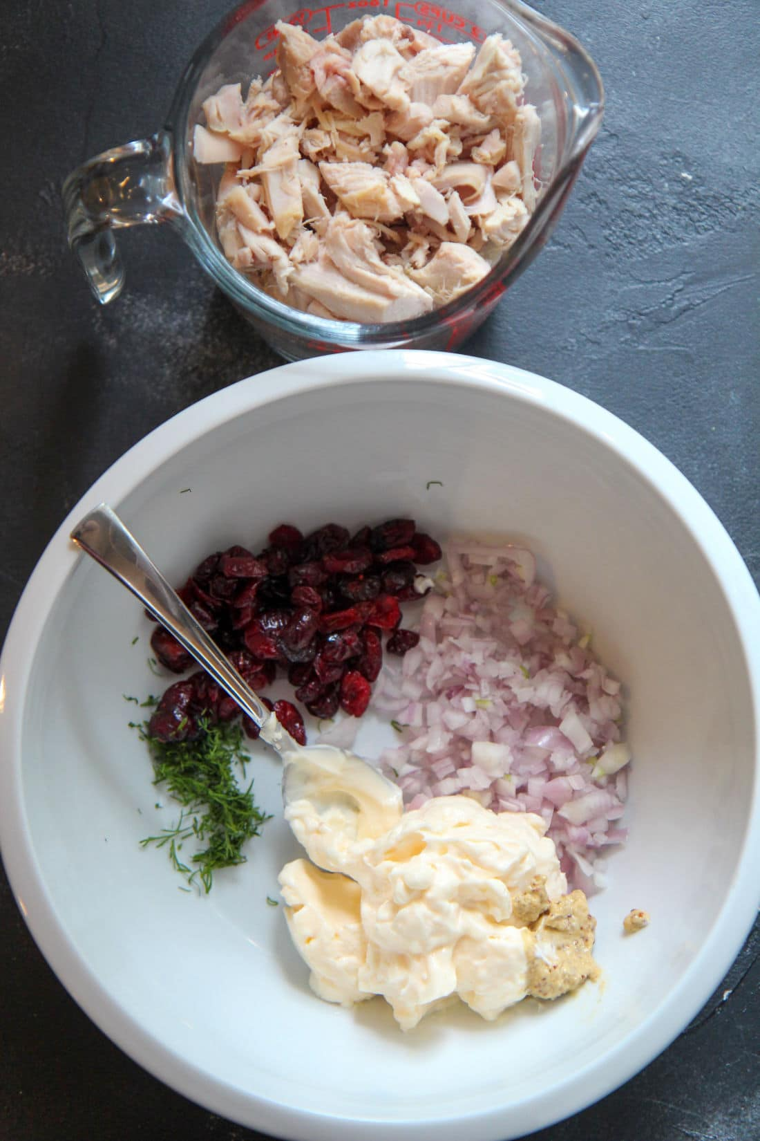mayo, shallots, cranberries, and dill in a while bowl with a spoon and chicken in a cup