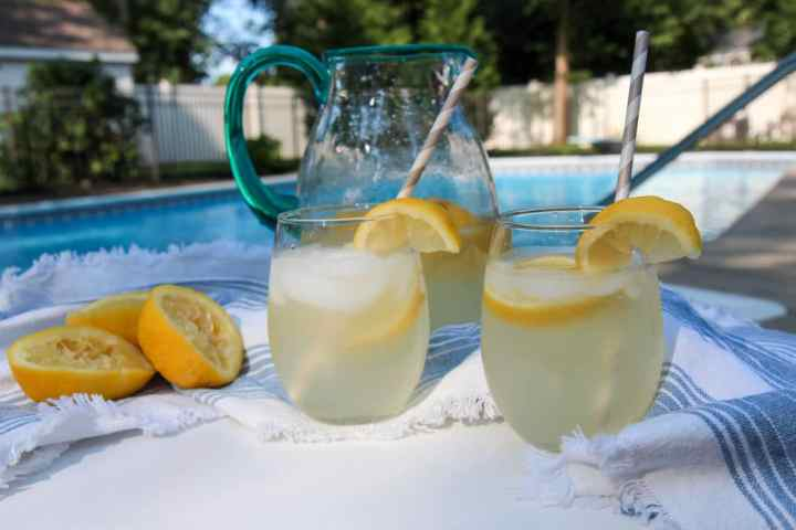 a pitcher and 2 glasses with fresh lemonade outside by the pool.