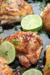 bone in chicken thighs in a cast iron skillet with lime wedges