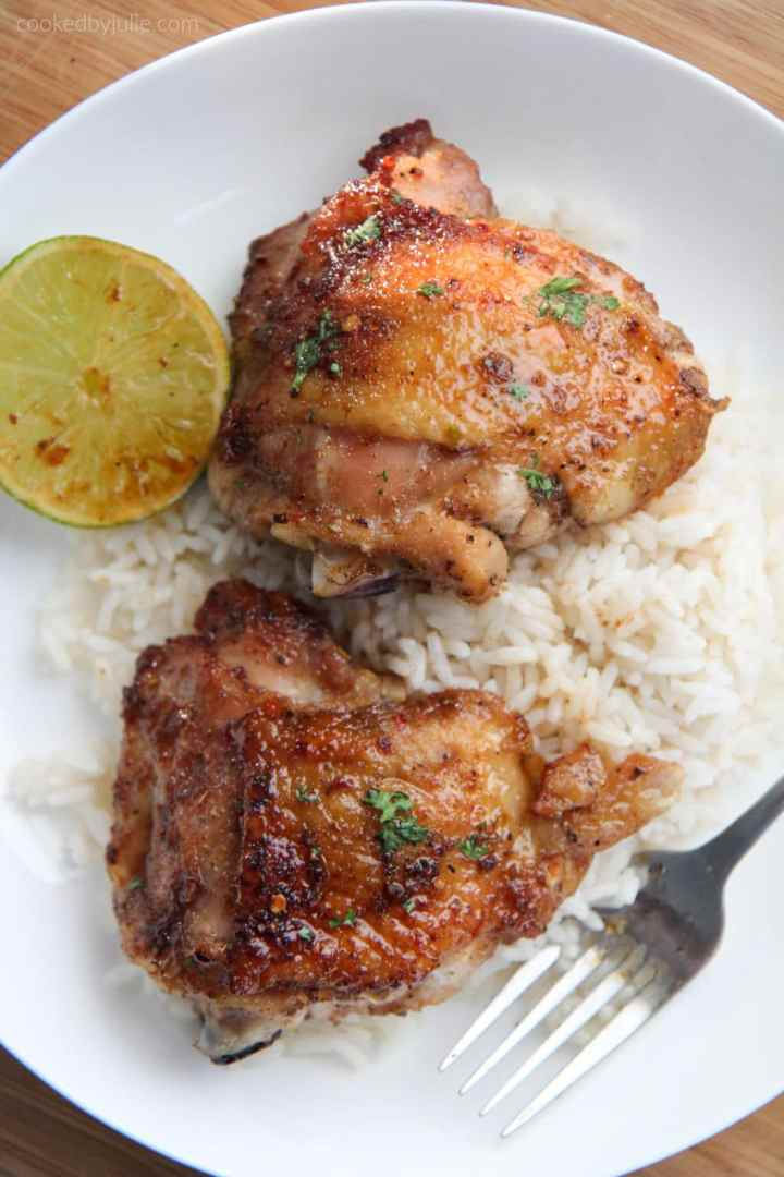 two honey lime chicken thighs on top of rice on a white plate with a fork and lime wedge