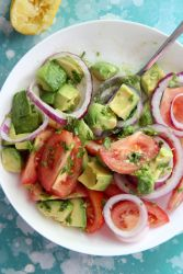 tomatoes and avocado salad in a white bowl with a lemon on the side