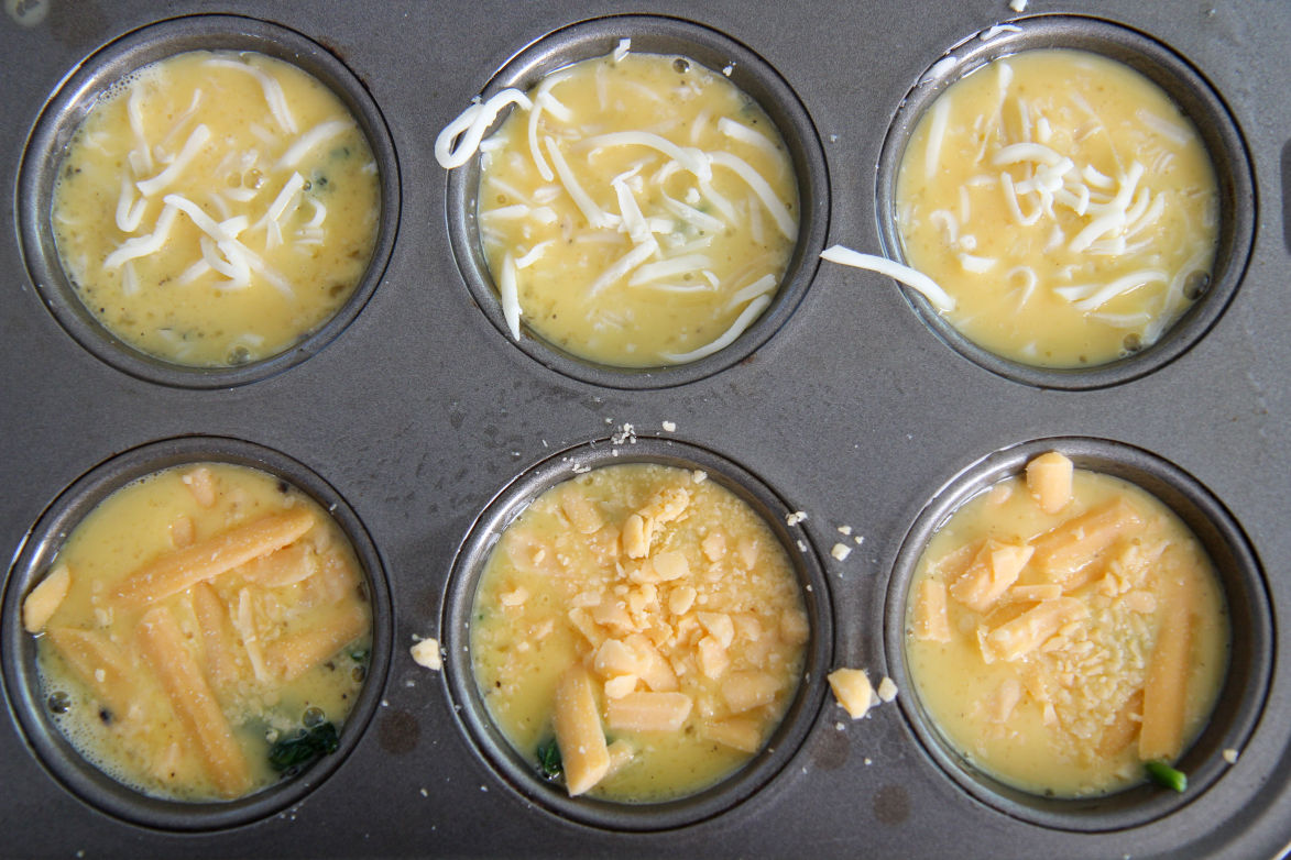 six scrambled eggs with spinach and cheese in a muffin tin