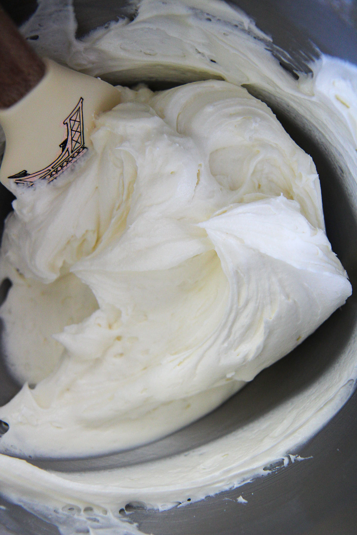 cream cheese frosting in a bowl with a spatula