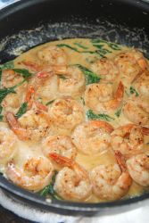 shrimp, cream sauce, and spinach, in a black skillet