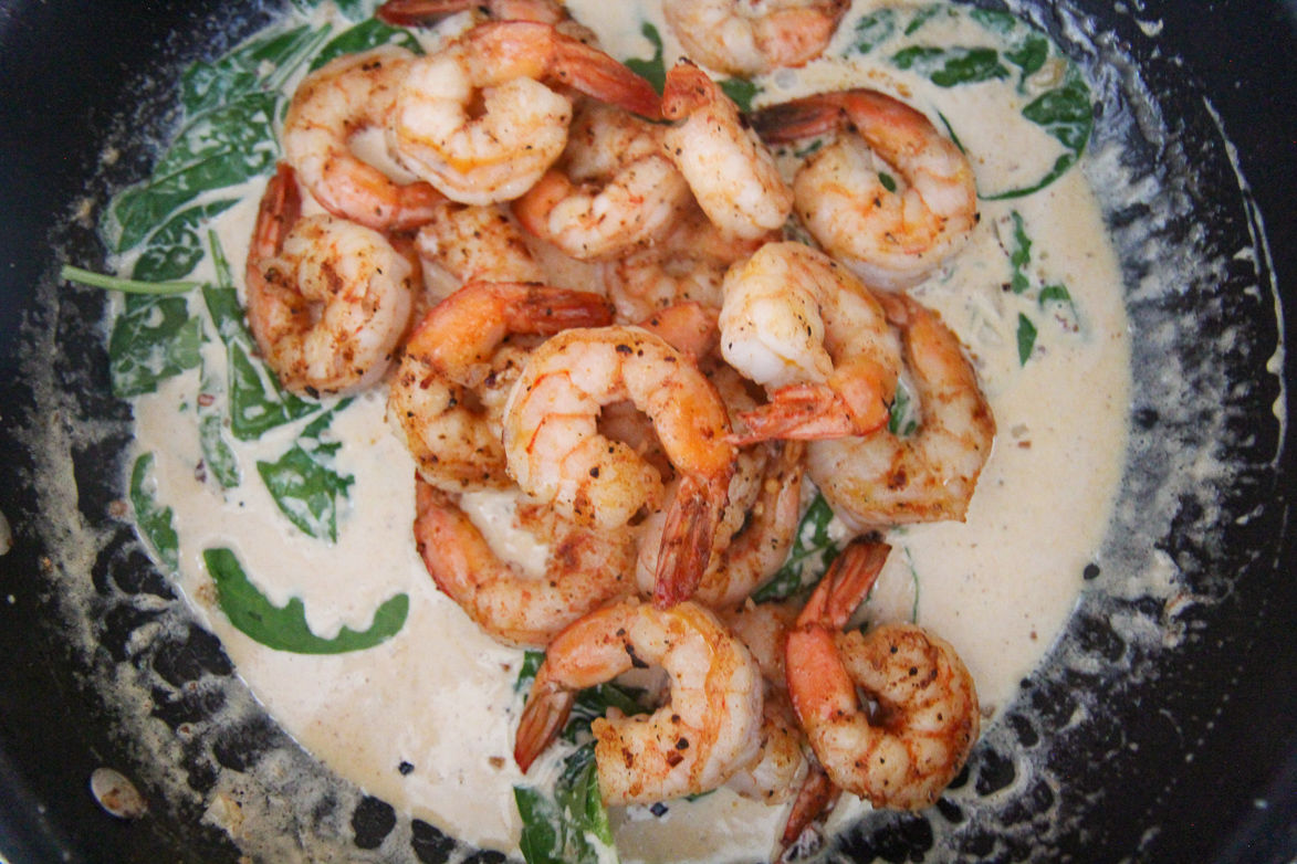 shrimp, spinach, and cream sauce in a black skillet
