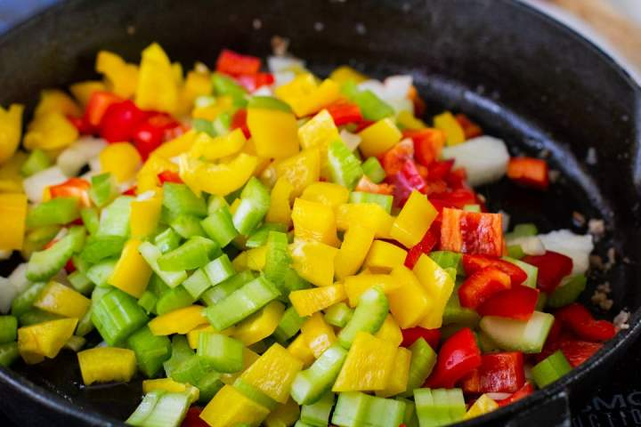 peppers, celery, and onions cooking in a cast iron skillet