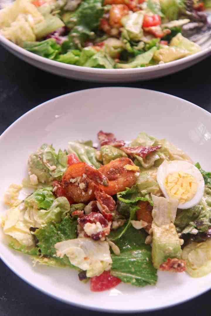 a small plate of shrimp cobb salad with a fork and bowl in the background