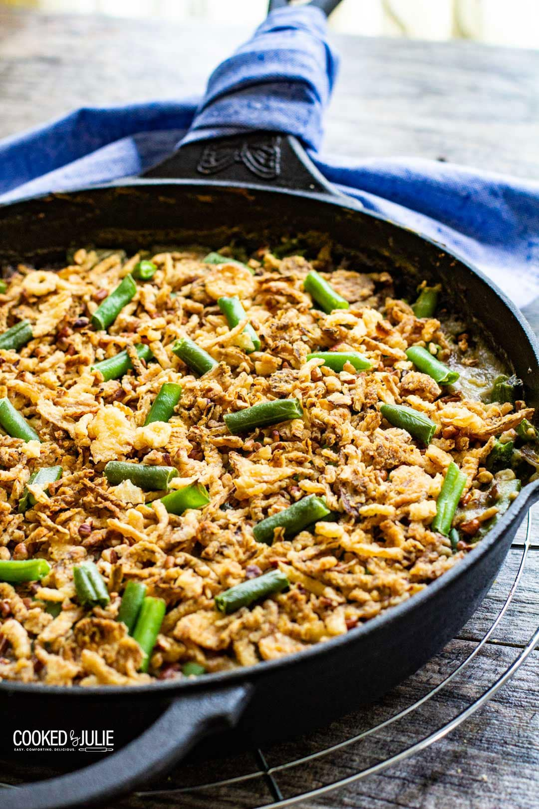 green bean casserole in an iron skillet with a blue towel