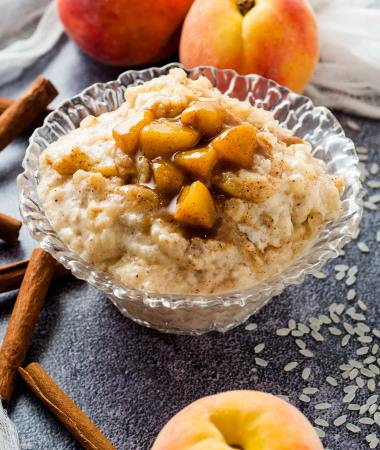 rice pudding and peaches in a glass bowl with peaches on the side