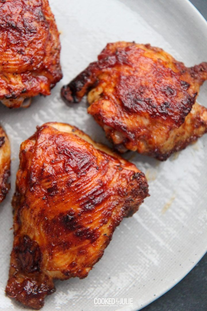three bbq chicken thighs on a gray plate
