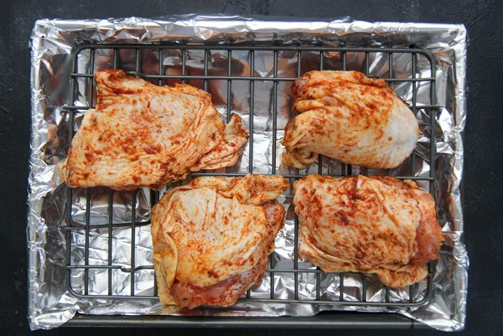 four pieces of raw seasoned chicken on a grill