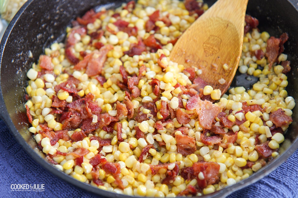 corn and bacon in a skillet with a wooden spoon