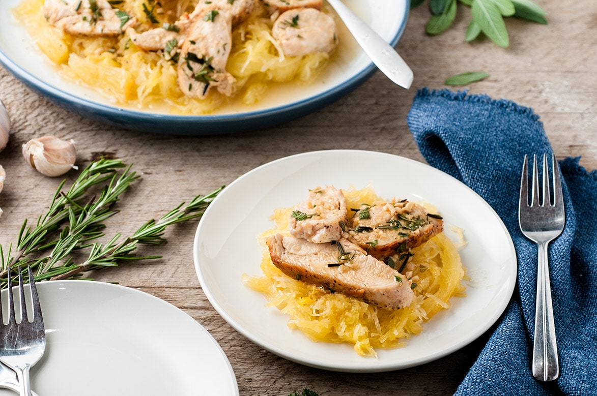 spaghetti squash with garlic chicken on a white plate with a fork