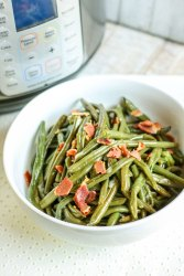 an instant pot and a small bowl of green beans on the side