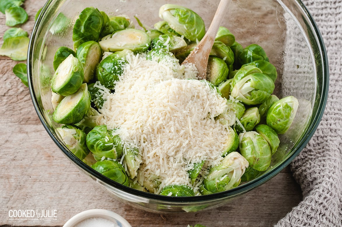 parmesan cheese and brussel sprouts with a wooden spoon in a bowl