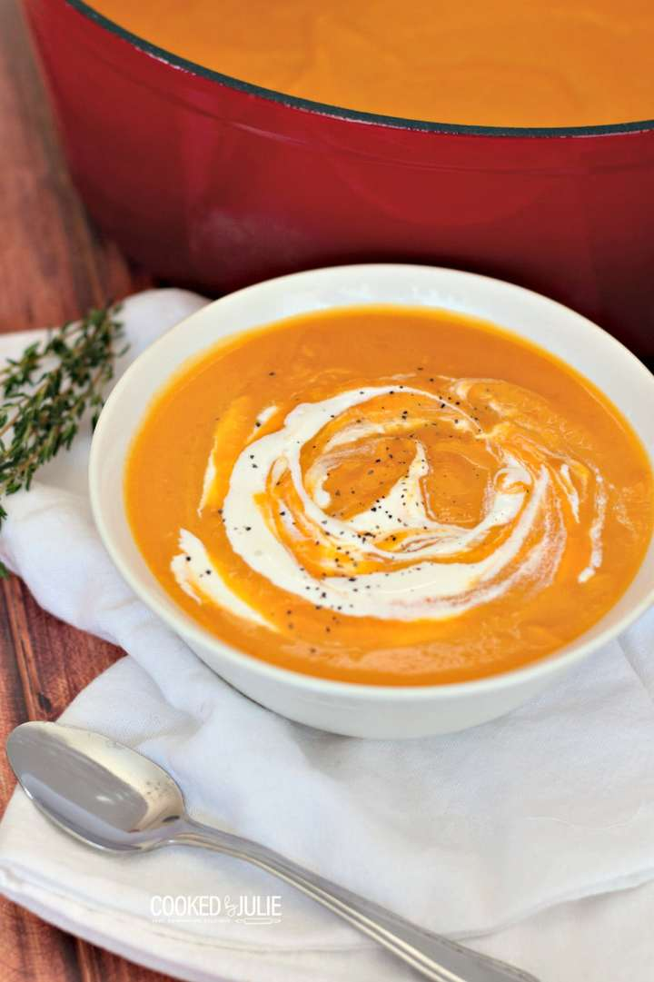 roasted butternut squash soup in a white bowl with a spoon on the side