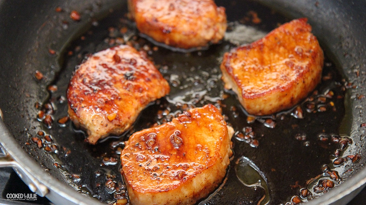 four pork chops with honey sauce in a black skillet.