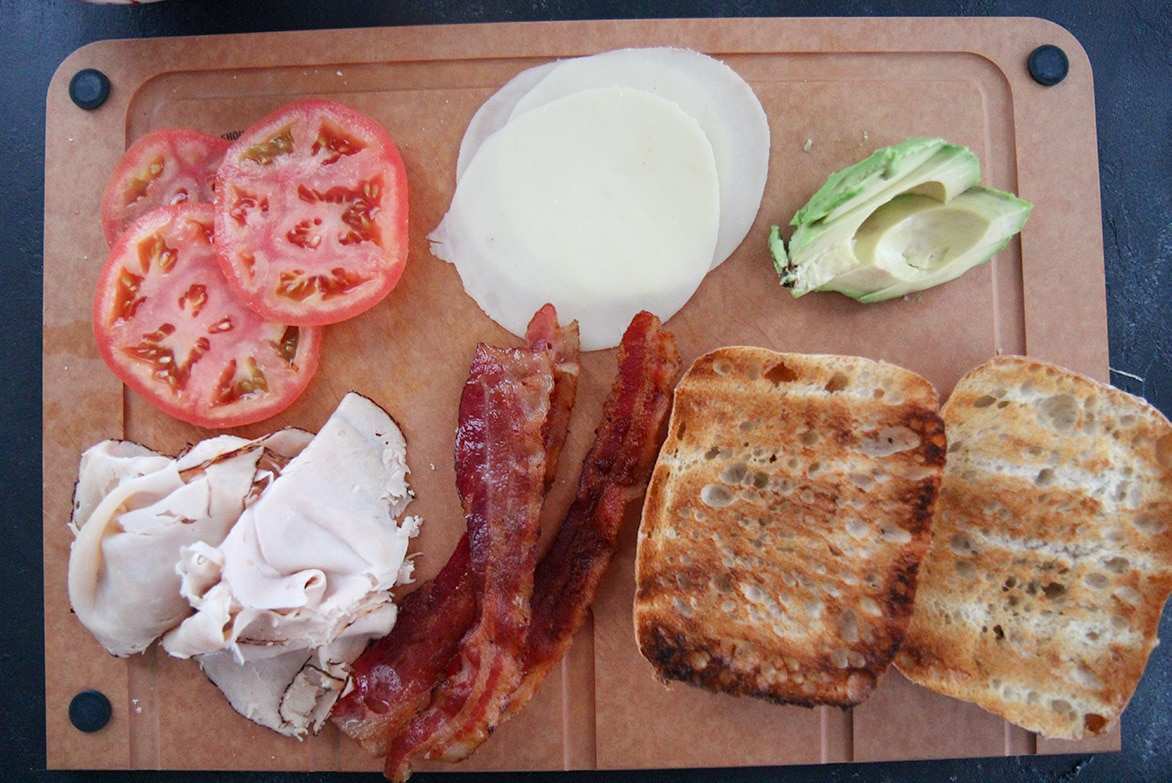 tomatoes, bacon, turkey, cheese, avocado, and bread on a wooden board