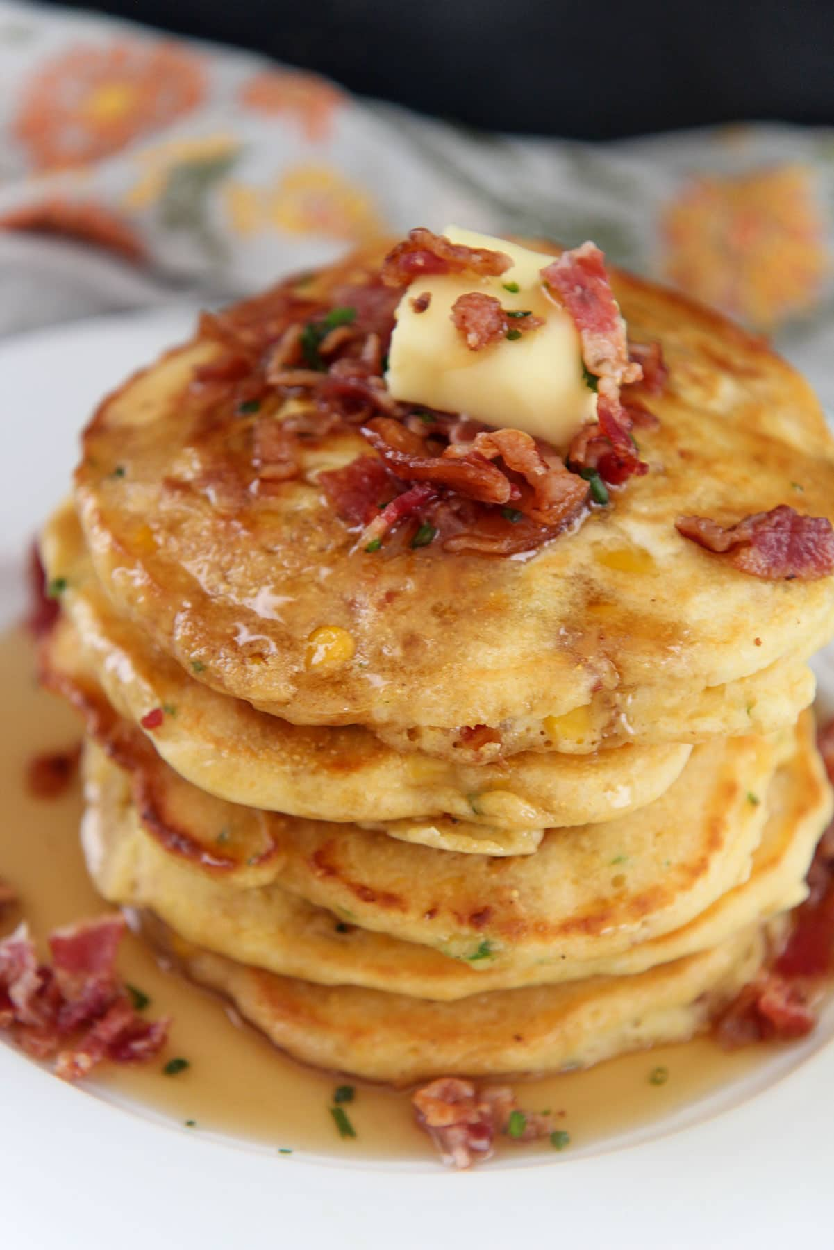 a short stack of bacon and corn pancakes on a white plate with syrup on top.