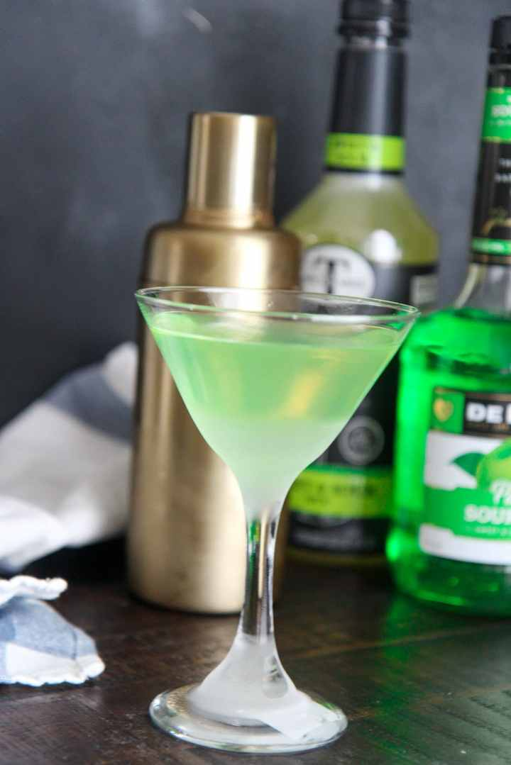 green appletini with a shaker and apple pucker alcohol in the background