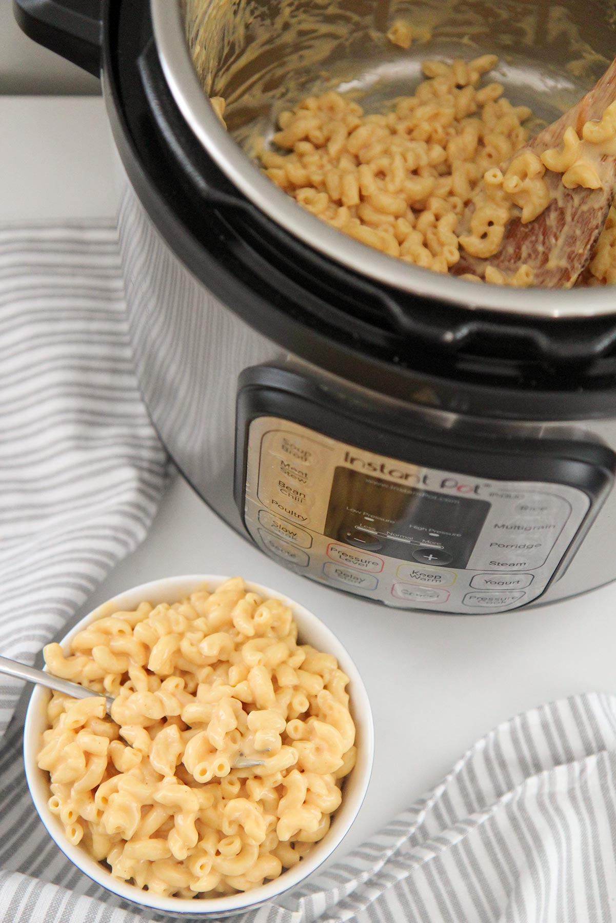 a small bowl filled with mac and cheese and an instant pot with mac and cheese in the background.