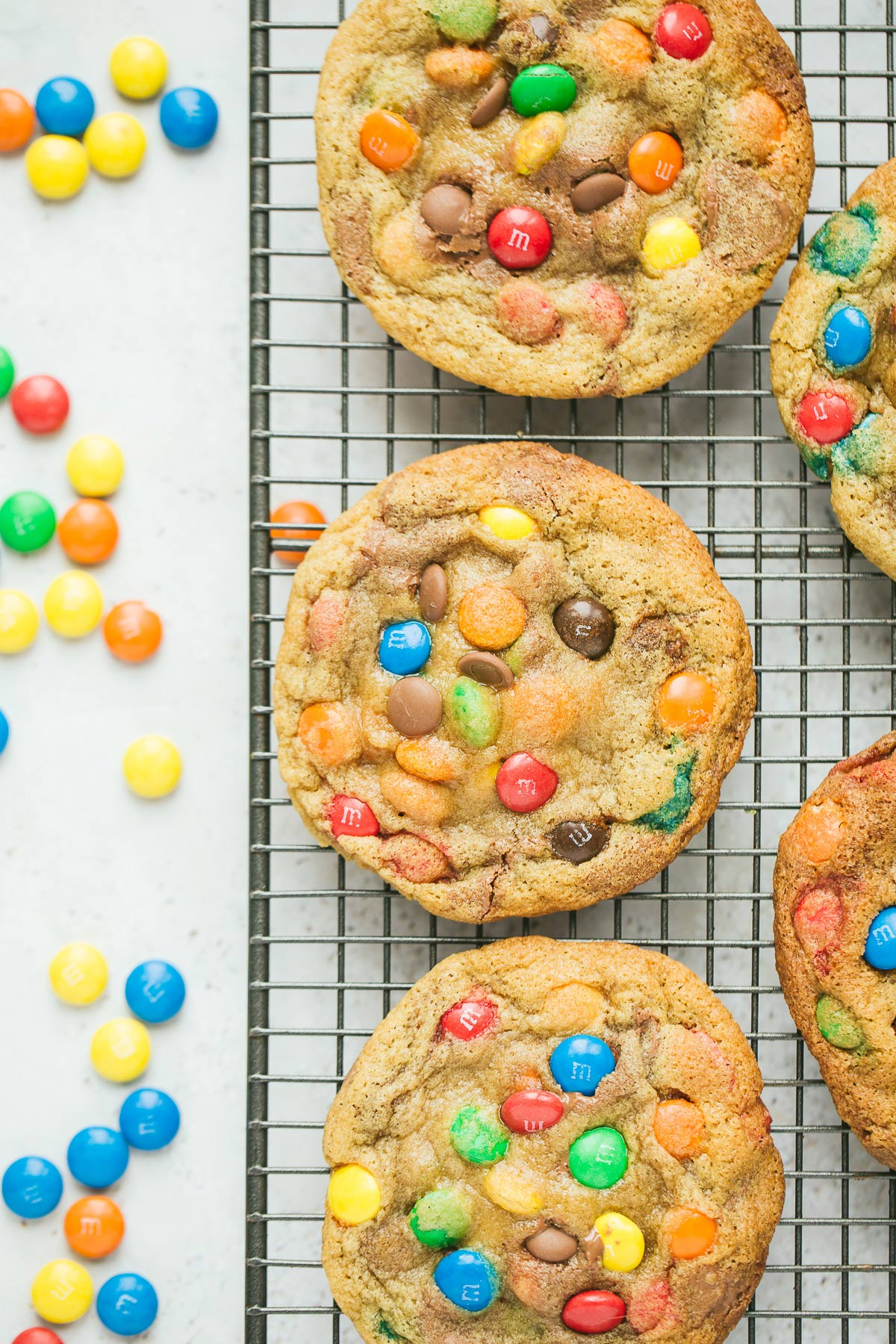 five m&m cookies on a wire rack with m&m candies on the side.