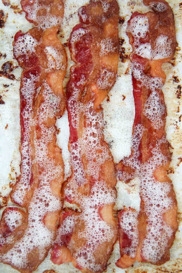 three slices of crispy cooked bacon on a baking sheet.