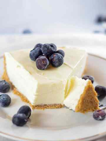 a fork slicing into a slice of cheesecake.