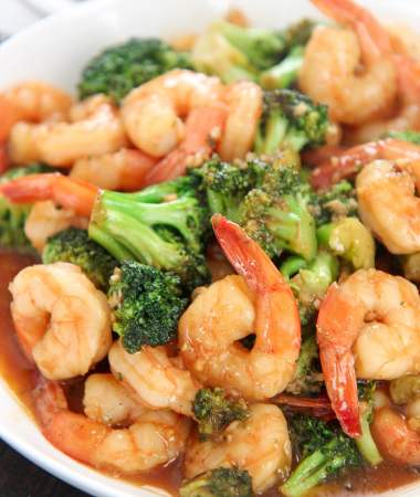 shrimp and broccoli with sauce in a white plate.