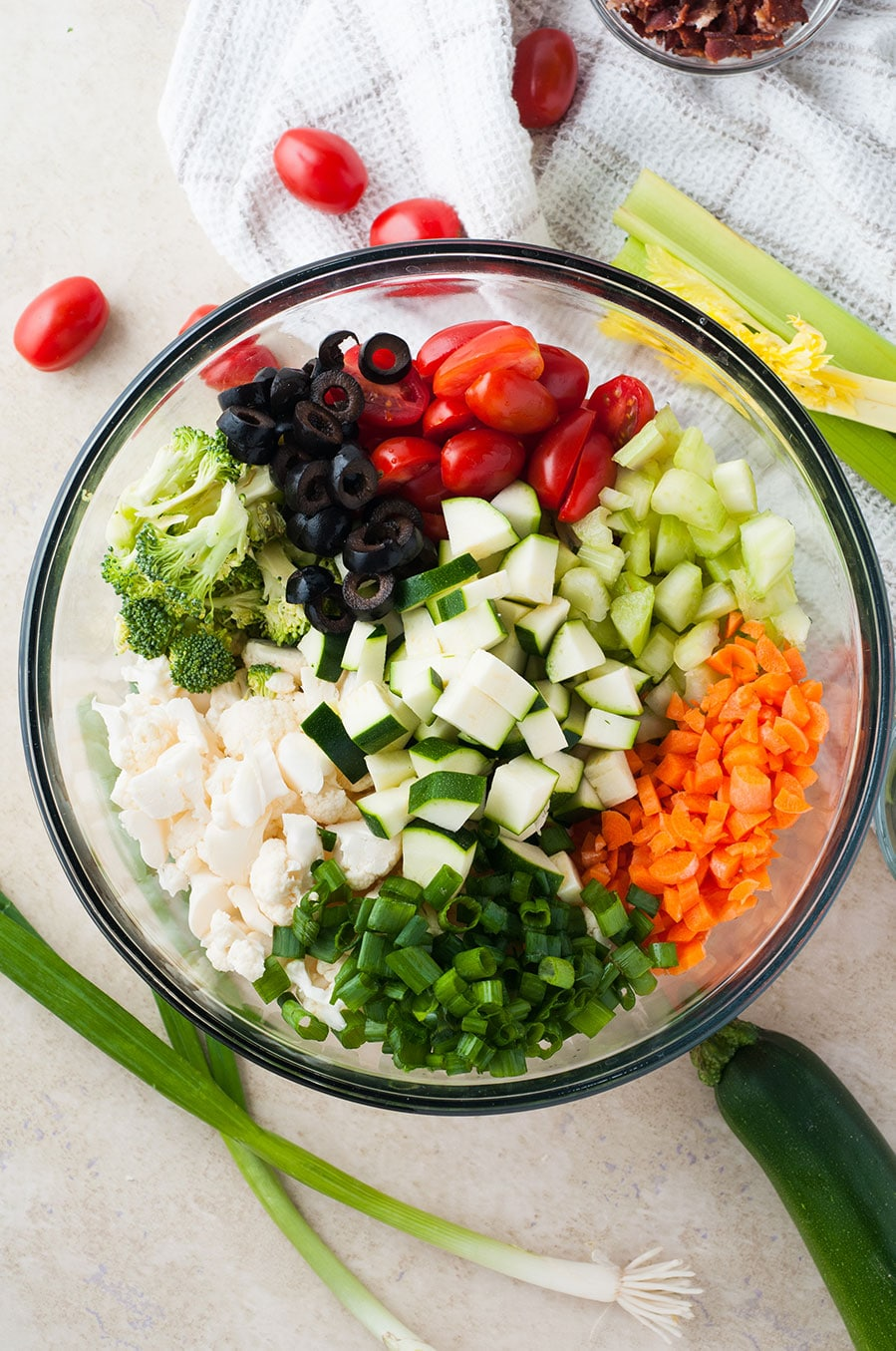 a large bowl filled with carrots, zucchini, broccoli, black olives, tomatoes, and cauliflower.