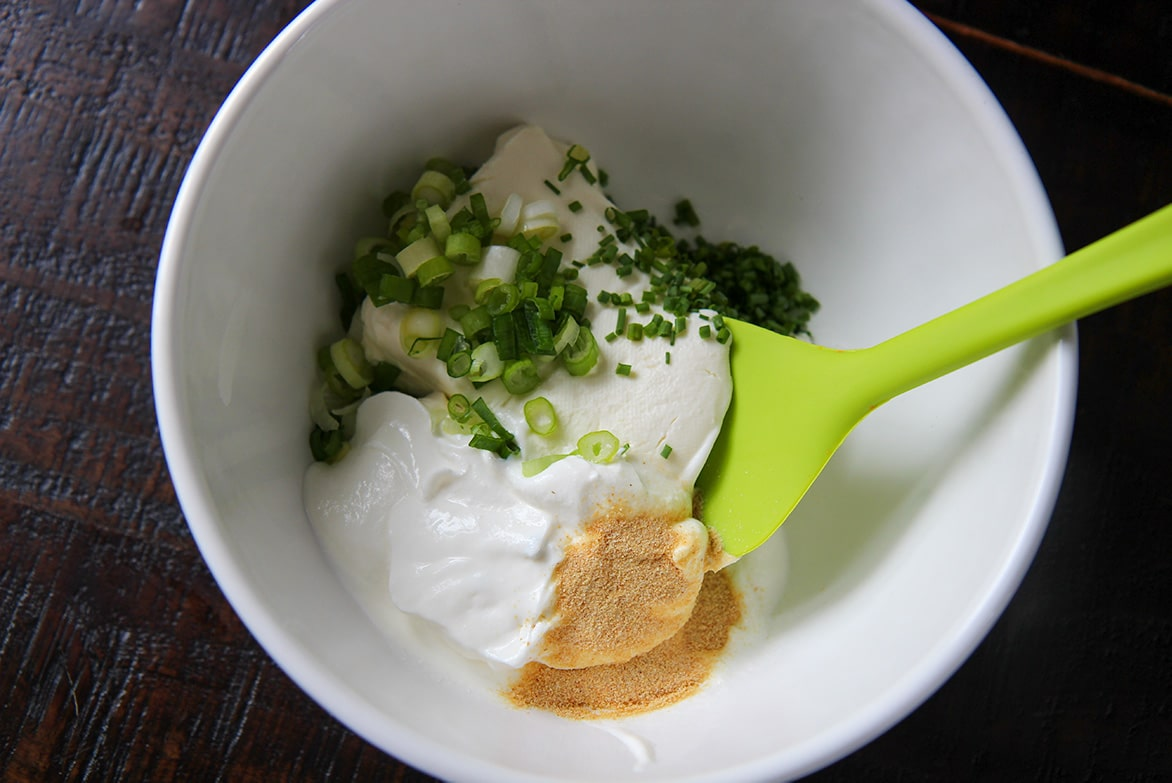 cream cheese, sour cream, granulated garlic, chives, scallions, and a green spatula in a white bowl.