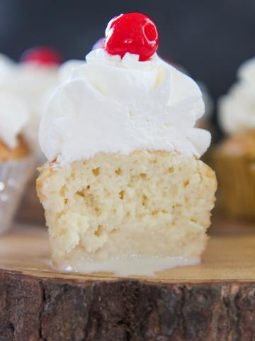 The inside of a tres leches cupcake with whipped cream and a cherry on top. Placed on a wooden surface.