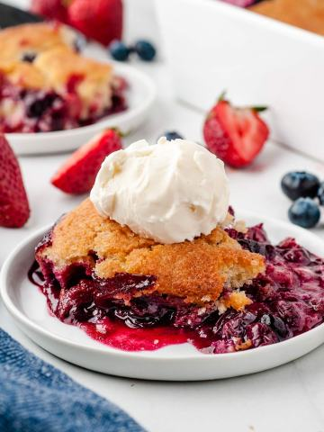 berry cobbler on a white plate with vanilla ice cream on top. berries and a baking dish in the background.