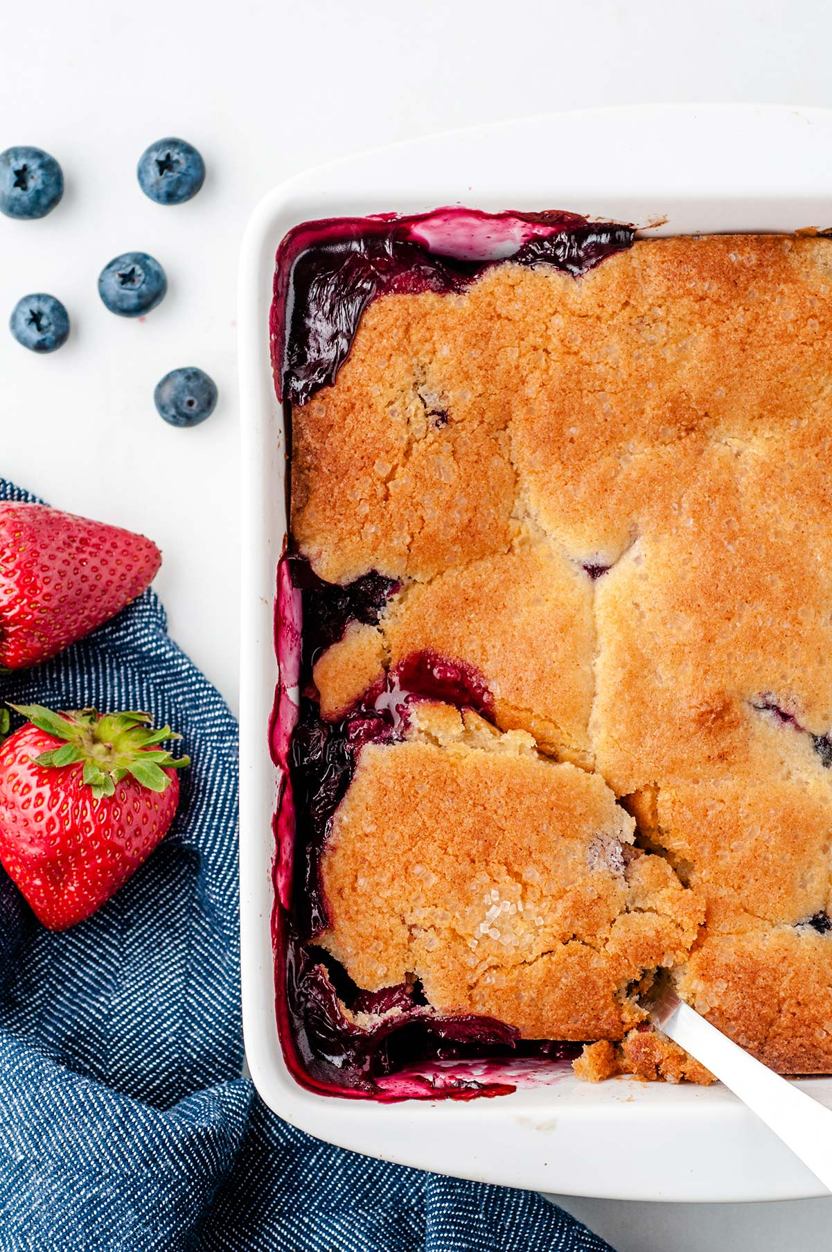half of a white baking dish with a baked berry cobbler. blueberries, strawberries, and a blue towel on the side.