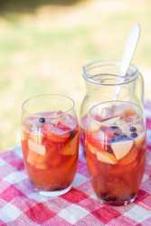 two glasses filled with sangria and fruit on top of a red and white table cloth and a pitcher with sangria in the background.