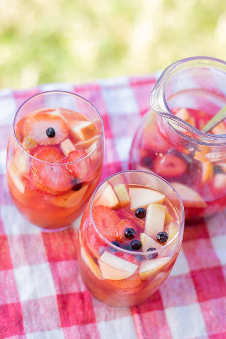 two glasses filled with mango sangria on a picnic table outside. With a pitcher in the background filled with sangria.