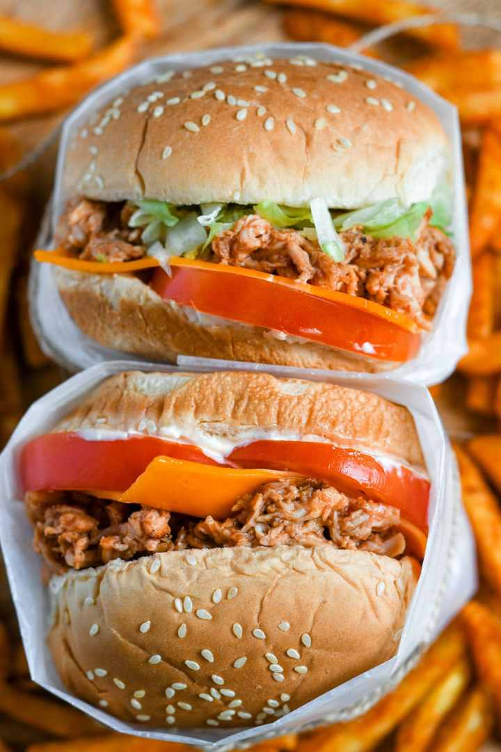 two chicken sandwiches stacked with sweet potato fries underneath.