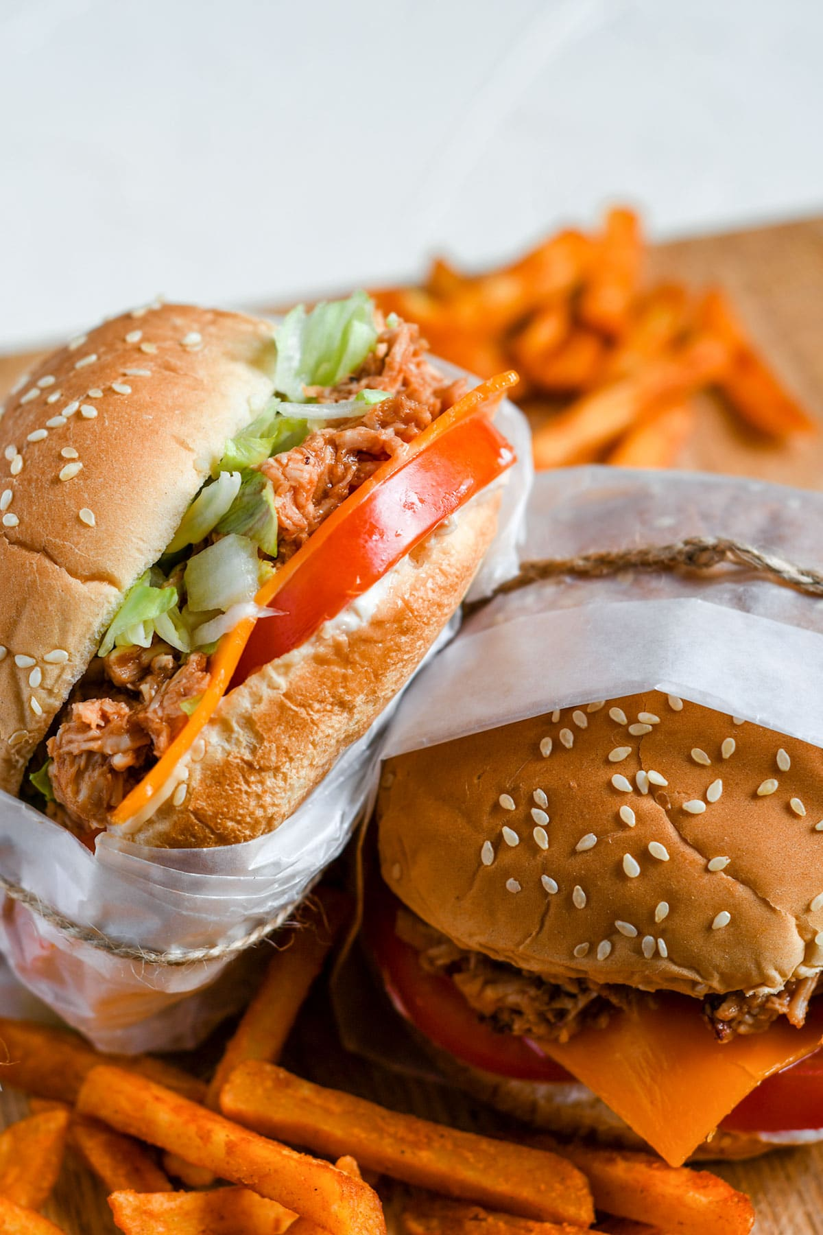 two shredded chicken sandwiches with lettuce, tomato, cheese, and sweet potato fries on the side.