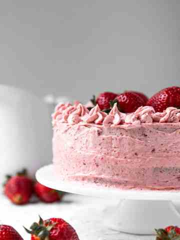 two layer fresh strawberry cake on a white cake stand with a white pitcher in the background and strawberries on the side.