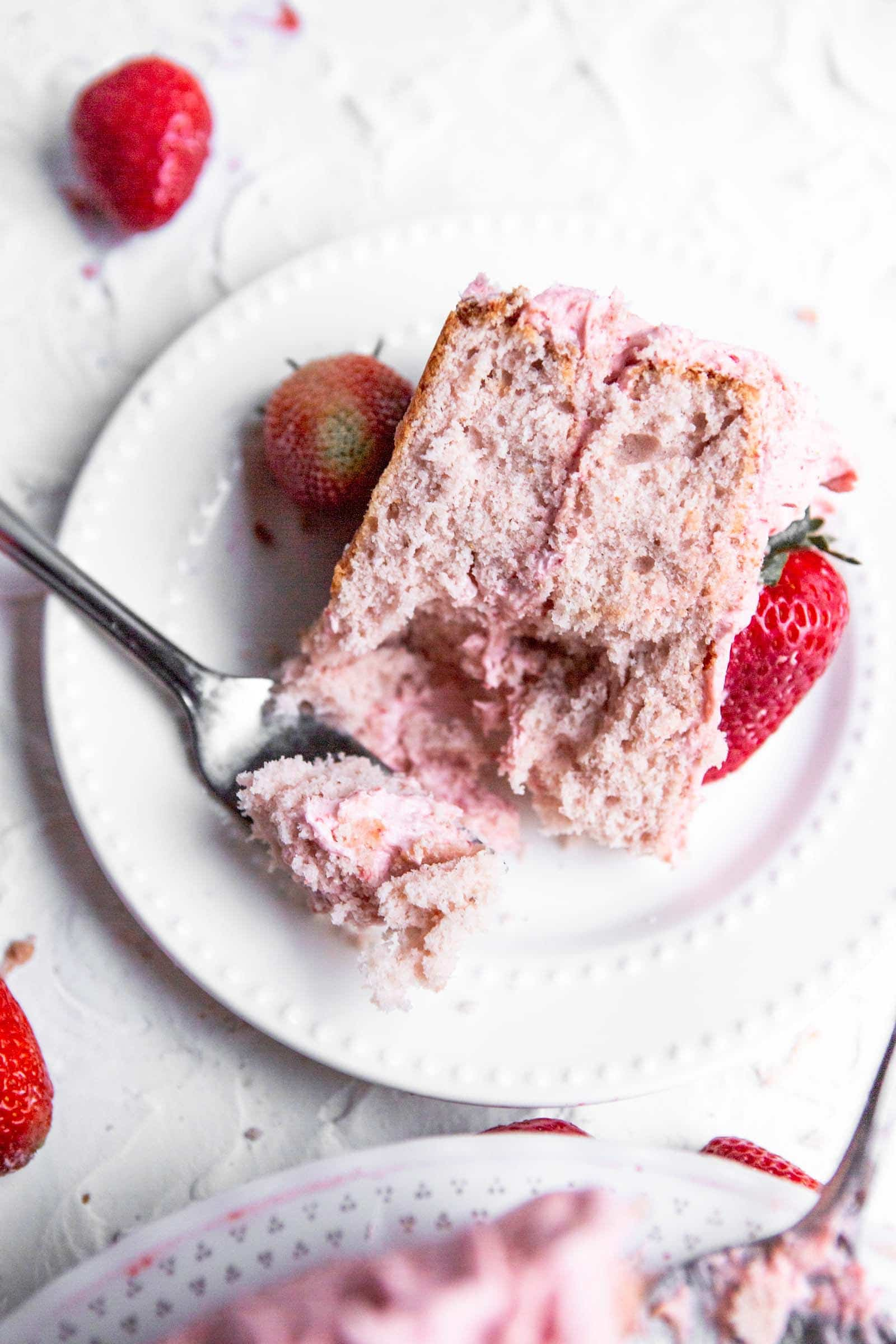 a slice of a two layer pink cake on a white plate with a fork and strawberries on the side.