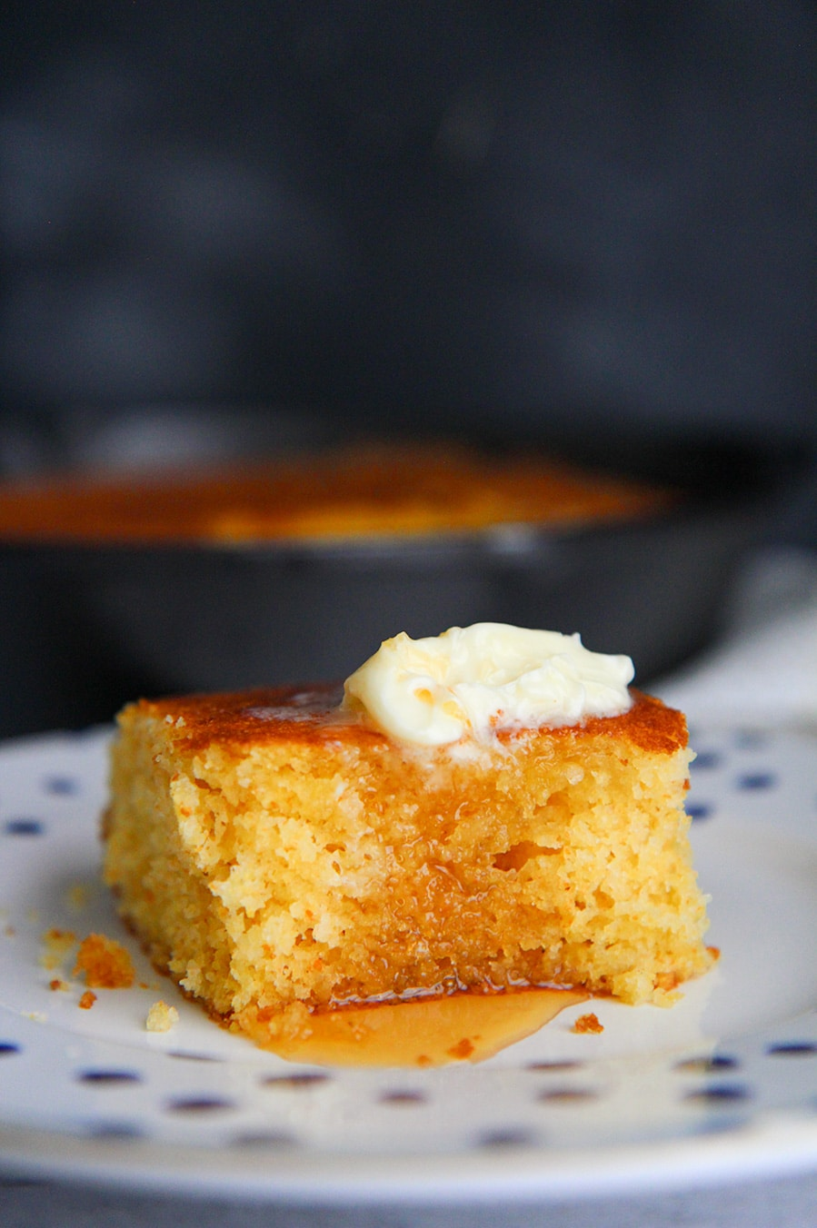 a slice of cornbread with butter and honey on a plate.