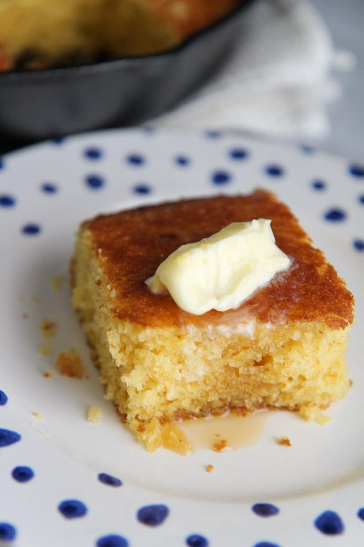 a slice of cornbread on a white plate with blue dots.
