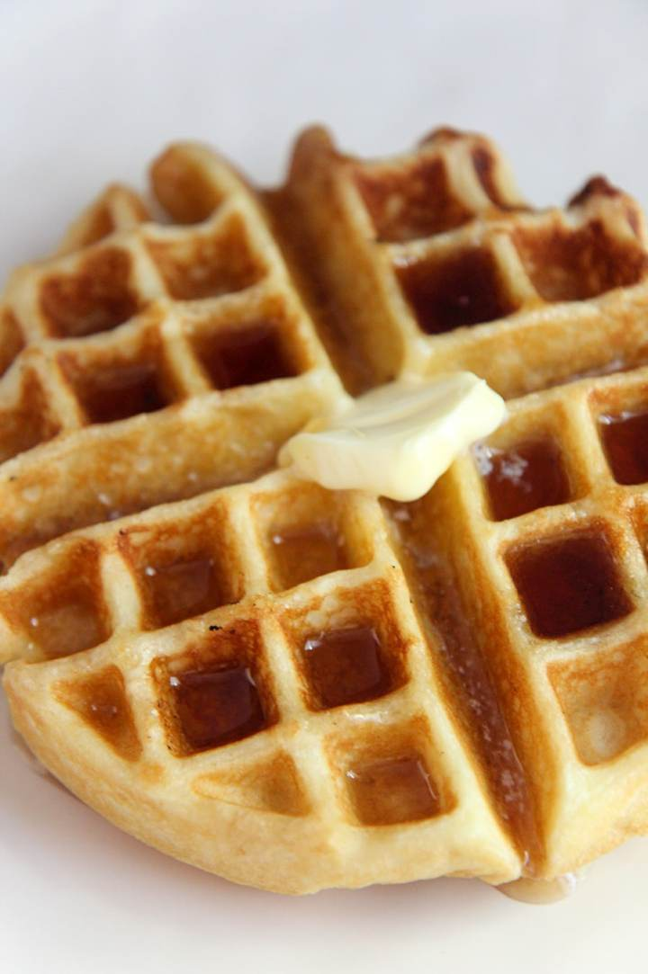 buttermilk waffle with syrup and butter on a white plate up close.