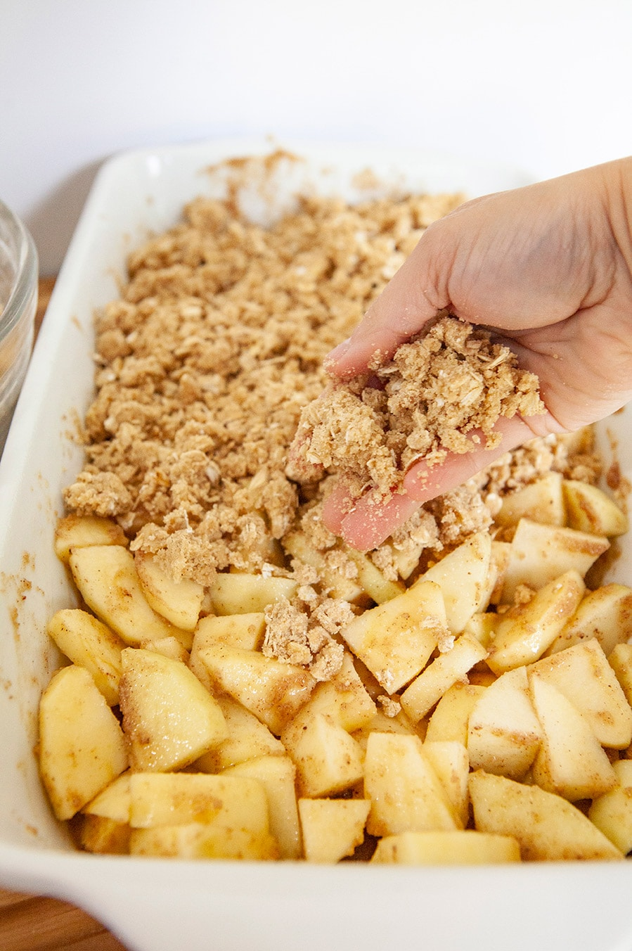 a hand pouring the oat topping over apples in a white casserole dish.