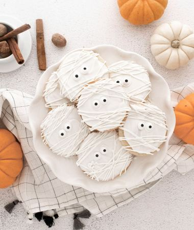 mummy cookies on a white plate with pumpkins on the side.